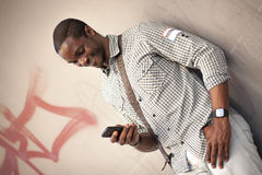 Young black man checking messages on his smart phone Royalty Free Stock Photo