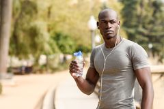Young black man drinking water before running in urban background. Young male exercising with naked torso listening to music with headphones stock photos