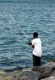 Young black man fishing. Off rocky shore Royalty Free Stock Photography