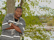 Young black man in front of a tree. Attractive African American man wearing chains with his arms crossed leaning against a tree outside Royalty Free Stock Images