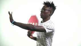 Black man with a sign of stop calling for and running away. A young black man with glasses holds a stop sign and calls for himself stock footage