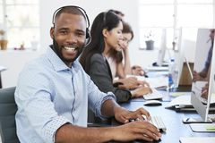 Young black man with headset on smiling to camera in office Stock Photos