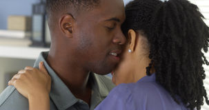 Young black man holding girlfriend and whispering into her ear Stock Photo