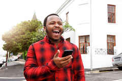 Young black man laughing with cellphone outside in city Royalty Free Stock Photo