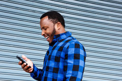 Young black man laughing with cellphone Stock Images