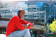 Young black man laughing in the city with mobile phone. Portrait of young black man laughing in the city with mobile phone Royalty Free Stock Photo