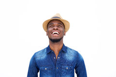 Young black man laughing and looking up against white background Royalty Free Stock Photography