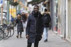 Young Black Man Listening to Earphones Posing on Sidewalk
