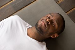 Young black man lying in Dead Body exercise. Photo of young black man lying in Dead Body exercise or Corpse pose with his eyes closed, Savasana pose, working out Stock Images