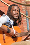 Young black man playing guitar. Happy young African American man playing the guitar in the city Royalty Free Stock Image