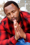 Young black man praying with eyes closed Stock Photography