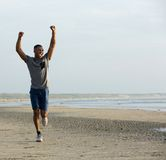 Young black man running on beach with arms raised Royalty Free Stock Photos