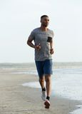 Young black man running on beach Royalty Free Stock Photo