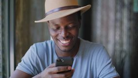 Young black man sits in a trendy cafe. Handheld portrait shot of smiling and laughing young black man texting message or email in his smartphone, sitting in stock video