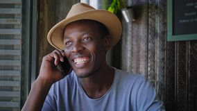 Young black man sits in a trendy cafe. Portrait of smiling and laughing young black man answering phone call and talking while looking at camera on his stock video