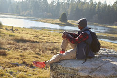 Young black man sitting alone on a rock in countryside Royalty Free Stock Photos