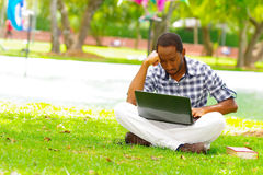 Young black man sitting down on green grass and working in his computer in the city of Quito Ecuador Royalty Free Stock Photo