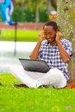 Young black man sitting down on green grass and working in his computer and listening music with his headphones posing. His back in a tree in the city of Quito Royalty Free Stock Image