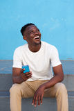 Young black man sitting on steps with cell phone and laughing Stock Image