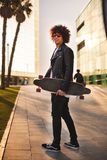 Young black man with skateboard walking in street and looking royalty free stock photography
