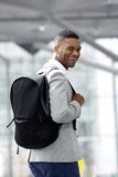 Young black man smiling with bag at airport Royalty Free Stock Photo
