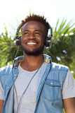 Young black man smiling with headphones outside Royalty Free Stock Photography