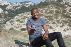 Young black man smiling, outdoor. Young black man smiling and reaching out his hand to camera, sitting on ground at the seaside Royalty Free Stock Image