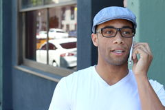 Young black man smiling and talking on mobile phone outside with copy space Stock Photography