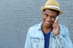 Young black man smiling and talking on mobile phone outside with copy space on the left.  Royalty Free Stock Photo