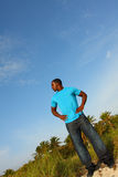 Young Black Man Standing Tall. At an angle with a blue sky background behind him Royalty Free Stock Photo