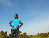 Young Black Man Standing Tall. With a blue sky background behind him Royalty Free Stock Photo