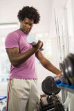 Young black man taking weights from rack in gym Stock Photo