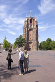 Young black man talks to older couple near old lopsided tower ol. Leeuwarden, Netherlands, 11 june 2017: young black man talks to older couple near old lopsided Stock Image