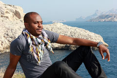 Young black man thinking, outdoor. Young black man looking far and thinking about something, sitting on the ground at the seaside Stock Images