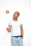Young black man throwing a red apple Stock Images