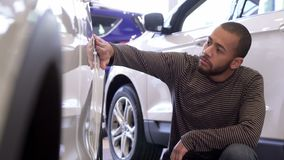 Man touches car wing at the dealership. Young black man touching car wing at the dealeship. Low shot of handsome african american guy turning his face to the Royalty Free Stock Image