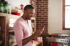 Young black man using smartphone in kitchen, close up stock photography