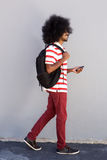 Young black man walking with bag and mobile phone. Full length portrait of young black man walking with bag and mobile phone Royalty Free Stock Photography