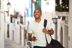 Young black man walking and listening to music with earphones and smart phone Royalty Free Stock Images