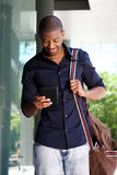 Young black man walking outside with bag and mobile phone. Portrait of young black man walking outside with bag and mobile phone Royalty Free Stock Photography