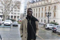 Young Black Man Wearing Beige Coat Posing in City