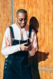 Young black man using smart phone outdoors. Young black man wearing casual clothes and sunglasses using smart phone against a wooden background. Millennial royalty free stock images