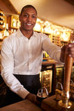 A young black man working behind a bar looks to camera Royalty Free Stock Photo