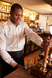 A young black man working behind a bar preparing drinks Stock Photo