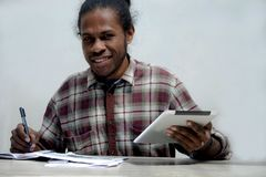 Smiling young black man working and studying holding laptop and pen doing homework royalty free stock images