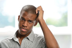 Young Black man worried. Worried black young man with hand on his head inside a building Royalty Free Stock Photography