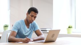 Young Black Man Writing on Paper, Paperwork. Young creative designer , good looking stock video footage