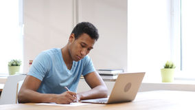 Young Black Man Writing on Paper, Paperwork royalty free stock images