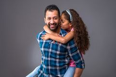 Young black dad with his daughter. A young black men standing and caring his daughter on his back while she giving him a kiss on his neckr Royalty Free Stock Photos