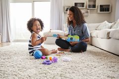 Young black mum plays ukulele with toddler daughter at home stock photography